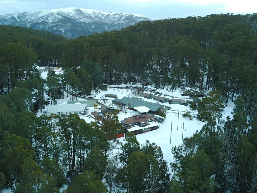 An aerial image of Howmans Gap Alpine Centre during the winter snowfall.